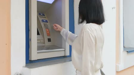 bankomat : young woman inserting a credit card to ATM, beautiful girl banking, business woman after work in bank, shopping mall