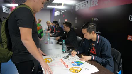 bálvány : MOSCOW, RUSSIA - OCTOBER 27 2018: EPICENTER Counter Strike: Global Offensive esports event. Team Avangar players on autograph session with a fans. Fan recieves handshake and selfie with his idol.