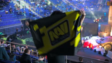 MOSCOW, RUSSIA - OCTOBER 27 2018: EPICENTER Counter Strike: Global Offensive esports event. Happy beautiful girl fan at arena with team Natus Vincere NaVi flag. Cheering, looking at camera and smiling.
