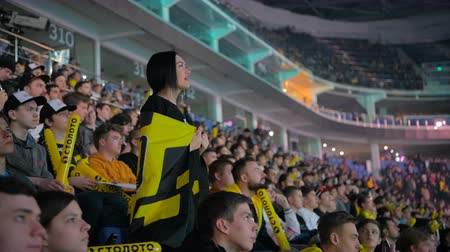 MOSCOW, RUSSIA - OCTOBER 27 2018: EPICENTER Counter Strike: Global Offensive esports event. Happy beautiful girl fan at arena with team NaVi flag. Cheering with a hands raised and smiling. Stok Video