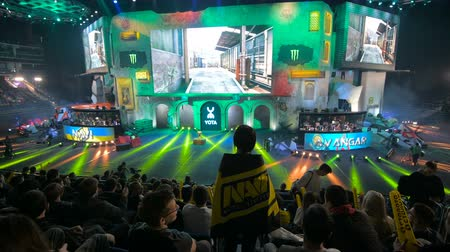 MOSCOW, RUSSIA - OCTOBER 27 2018: EPICENTER Counter Strike: Global Offensive esports event. Happy beautiful girl fan at arena with team NaVi flag watching the game and clapping hands.