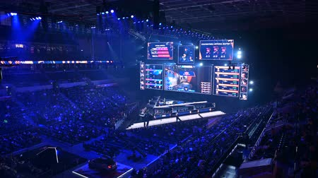 torcendo : MOSCOW, RUSSIA - 14th SEPTEMBER 2019: esports Counter-Strike: Global Offensive event. Main stage with a big screen showing the matchs game moments. Arena lit with a red color.
