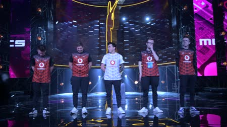 forma : MOSCOW - 23th DECEMBER 2019: esports event. Team Mousesports comes to the stage and welcomes the arena audience before the match start. Cameraman from broadcasting team in front.