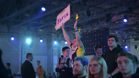 torcendo : MOSCOW - 23th DECEMBER 2019: esports event. Happy dedicated fan at arena. Cheering with a self-made poster with a hands raised.