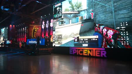 MOSCOW - 23th DECEMBER 2019: esports event. Big crowd on a stadium. Panoramic shot of a big venue, players on a stage, big screens with a game moments on it. Big crowd on a stadium. Stok Video