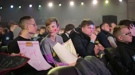 стример : MOSCOW - 23th DECEMBER 2019: esports event. Happy dedicated fan at arena. Cheering with a self-made poster with a hands raised.