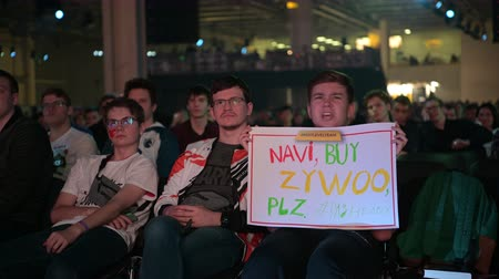 counter strike : MOSCOW - 23th DECEMBER 2019: esports event. Happy dedicated fan at arena. Cheering with a self-made poster with a hands raised.