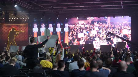 stávka : MOSCOW - DECEMBER 23 2019: esports gaming event. Main venue, lots fans with posters watching the game and supporting favorite teams. Big crowd at arena.