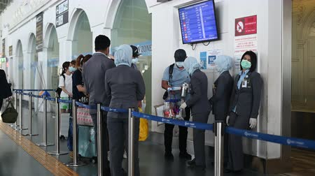 dünya çapında : Phuket, Thailand - March 04 2020: Passengers and airport staff wearing face masks at security control. Getting temperature checked for CoronaVirus before the flight.