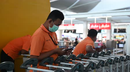 щит : Phuket, Thailand - March 04 2020. COVID-19 coronavirus infection. Airport staff wearing protective face mask against infectious diseases and as protection against pollution and the flu in Airport.