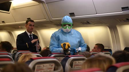 Moscow - March 04 2020. Temperature check on a corona virus at airplane. Medical official wearing infectious disease protection suite measure temperature of passengers inside the aircraft on arrival. Stok Video