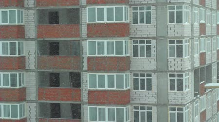 кирпичная кладка : Snowing in city with view to apartment house under construction. Close up snowy storm in city