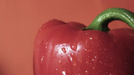 pimentas : Red bell pepper spray close up, drops of water going down, orange background