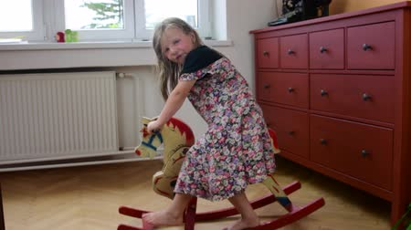 animal jovem : Cute little girl swinging on the rocking horse. Smalll girl wears flowered dress. Childhood concept. Stock Footage