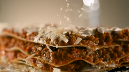 пармезан : Appetizing meat lasagna is sprinkled with pieces of grated cheese. Parmesan.Very beautiful studio shot. Slow motion.