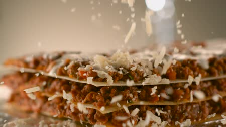 Appetizing meat lasagna is sprinkled with pieces of grated cheese. Parmesan.Very beautiful studio shot. Slow motion.