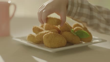 The childs hand takes an appetizing nuggets from the plate. Very beautiful studio shot. Slow motion.