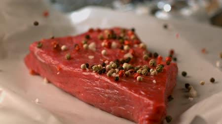 peas : Appetizing a piece of raw meat sprinkled with aromatic spices. Very beautiful studio shot. Slow motion.