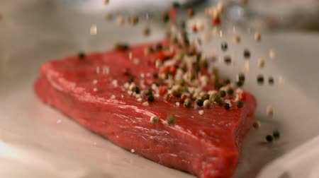 Appetizing a piece of raw meat sprinkled with aromatic spices. Very beautiful studio shot. Slow motion.
