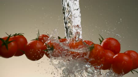 neutro : Flying tomatoes on a background of water. Very beautiful studio shot. Slow motion.