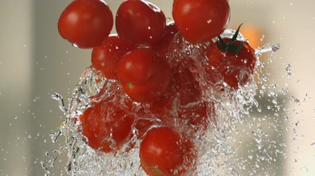 product of : Flying tomatoes on a background of water. Very beautiful studio shot. Slow motion.