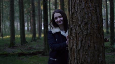Girl in the forest, peeping out from behind a tree
