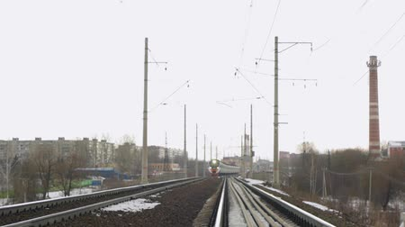 lokomotiva : Train departs from the city, cloudy weather
