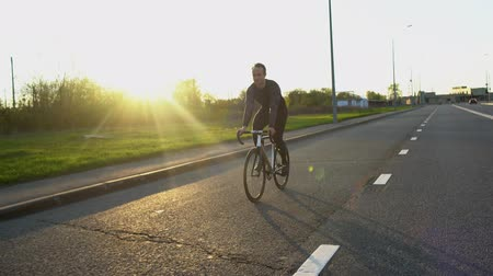 педаль : Man riding fixed gear bike on the road at sunset