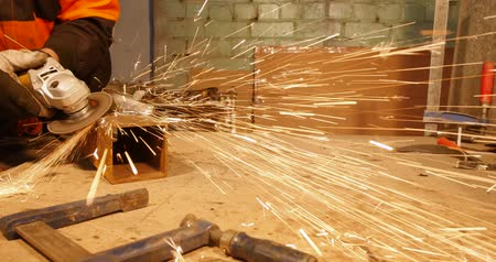 angle grinder : 4K - Metalworking. Sparks fly to the camera