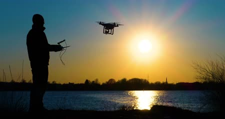 unmanned aircraft : 4K - Drone operator and drone silhouette. Quadcopter flies away