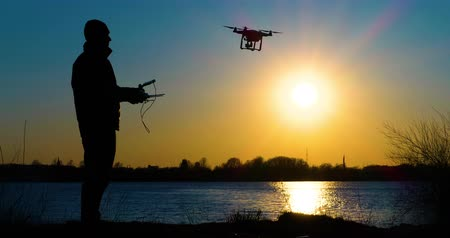fly away : 4K - Drone operator silhouette. Quadcopter flies up