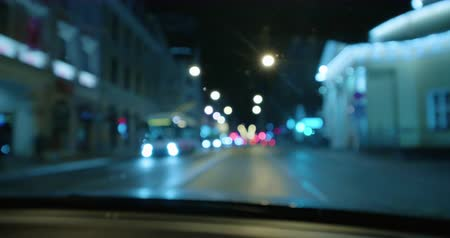 4K - Driving at night on town streets. Front car window with blurred city traffic Stok Video