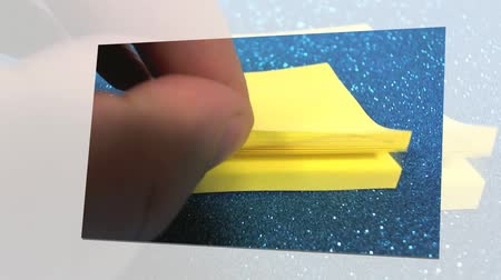 cork board : Close up footage of a person sticking a to do list on a cork board, of yellow color