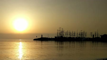 Sailing ships against the backdrop of the setting sun.