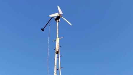 Homemade wind power generator against the blue sky.