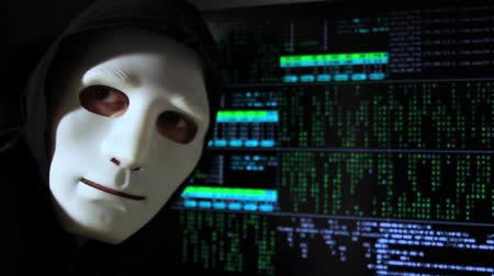 romsvetnik : A hooded man like a hacker works with digital data on the monitor and suddenly turns around. The face is covered with a mask.