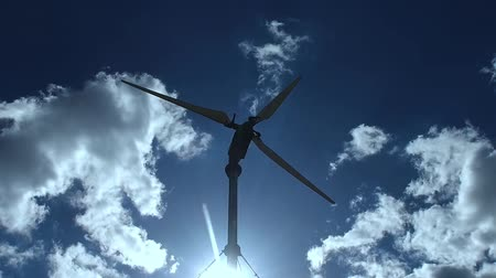 romsvetnik : The wind turbine is rotated in a sunny blue sky with clouds. Slow motion.