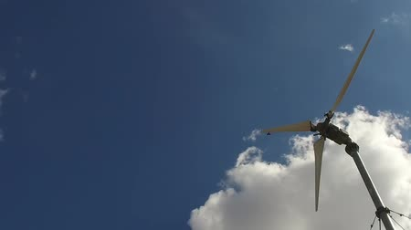 romsvetnik : The bird flies past the spinning screw of the wind turbine. Slow motion. Blue sky with clouds.