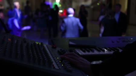 romsvetnik : The musician in the foreground adjusts the sound and plays the keyboard instrument. People dance in the background. Stock Footage