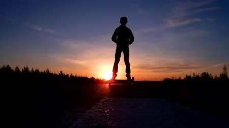 romsvetnik : Silhouette of the teenager on the hoverboard rides from the sunset. The camera moves from right to left.