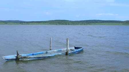 vazamento : Slow motion: The old wooden blue boat on the lake is chained, filled with water.