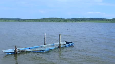 hava durumu : Slow motion: A lonely old flooded boat rocks on the waves of the lake. Stok Video