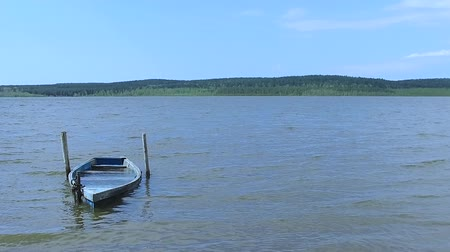 submerge : Slow motion: The old blue boat chained with a chain rocks on the waves on the lake.