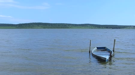 romsvetnik : Slow Motion: A wooden old boat of blue color on the waves of the lake is filled with water. Stock Footage
