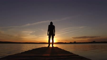 The man comes to the pier in the lake and looks at the sunset. Silhouette. Wideo