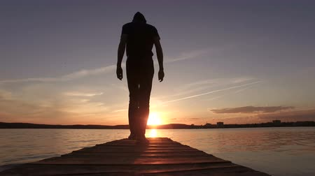 A silhouette of a man goes to the pier in the lake towards the sunset.