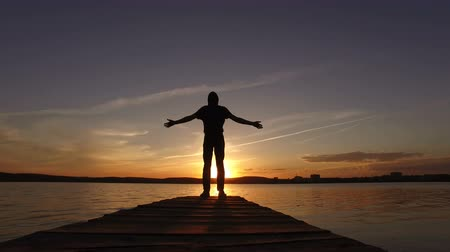 ilhouette of a guy on a dock for boats in the lake raises his hands up at sunset. Wideo
