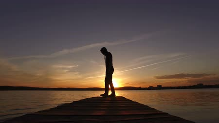 A man on the bridge in the lake goes from the sunset side to the foreground to the camera. Wideo