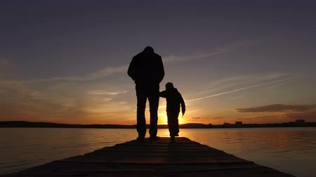 The man holds the boy by the hand and they walk along the pier towards the sunset on the lake. Wideo