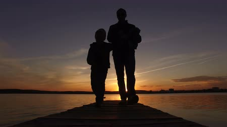The boy and dad are walking along the pier from the sunset on the lake. Wideo
